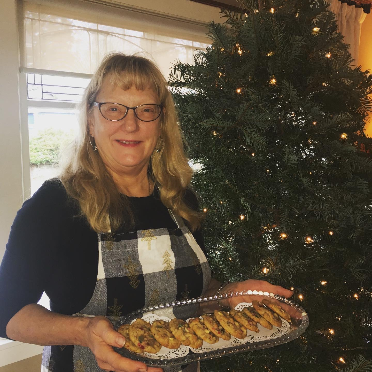 Woman holding tray of cookies in front of Christmas tree