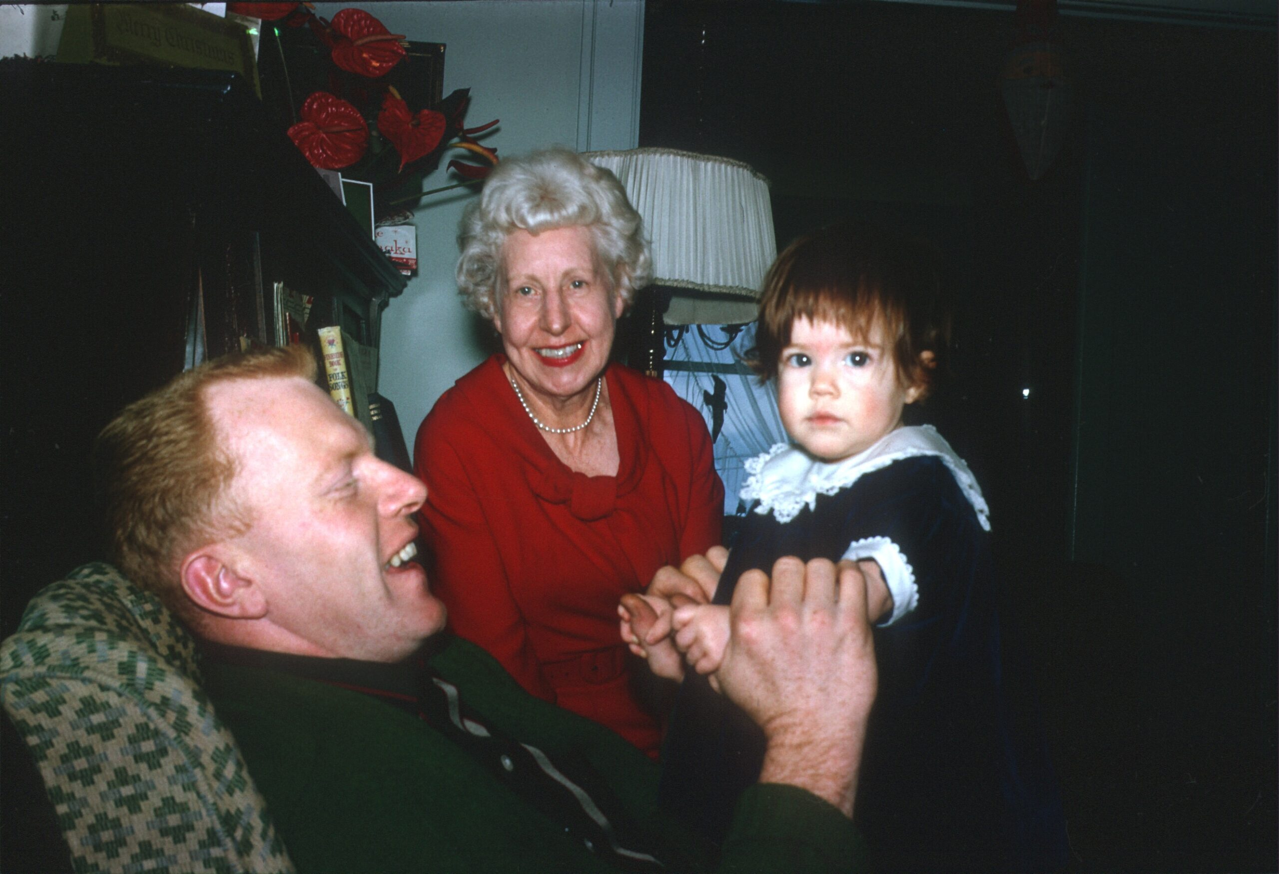 man holding baby with older woman looking on