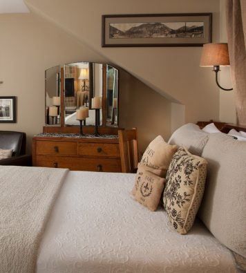 The bedsheets are beige and pillows look comfortable in the Cascade room