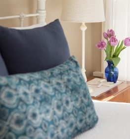 Pillows rest on the end of the bed and a bouquet of beautiful tulips is on the dresser