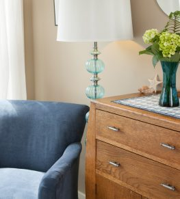 The wood dresser sits aside a nice blue chair with a bouquet of flowers atop it