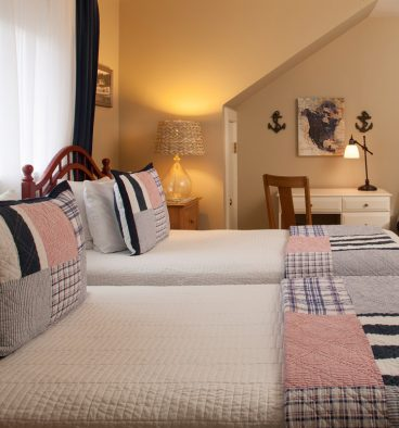 The Ballard Room has twin beds with tasteful pillows and blankets, with desk and chair for guests' convenience