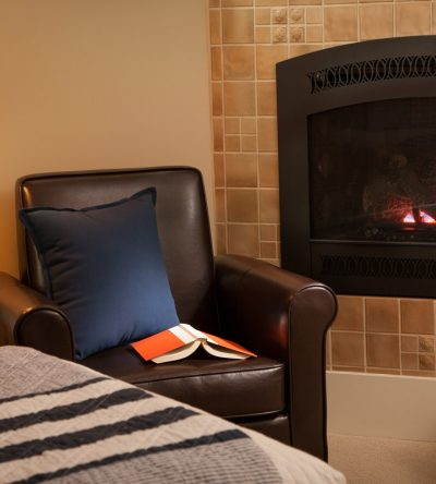 A book rests on a leather chair in the Ballard room with the fireplace on