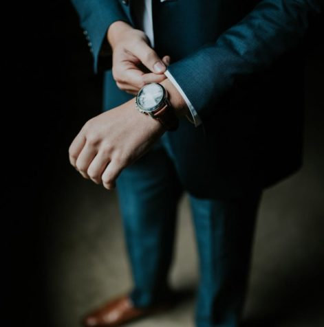 Business man adjusts his watch and the collar of his suit