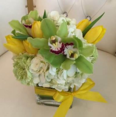floral arrangement of yellow tulips, white and purple flowers tied with yellow ribbon