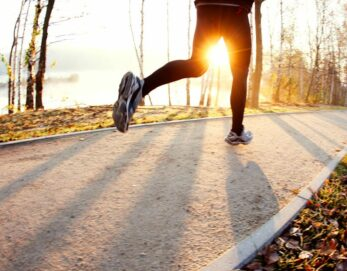 A jogger paces themselves lakeside in the early morning light