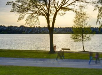 A shot of Green Lake midday with ripples on the water and people enjoying the park