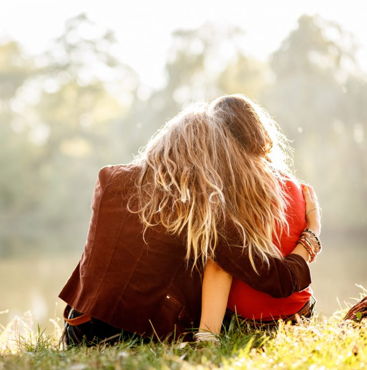 A friend hugs another while they sit on the grass