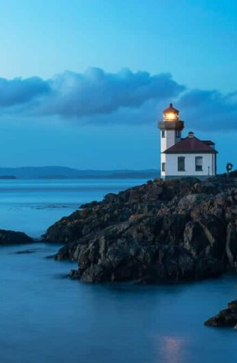 A lighthouse overlooks the pacific ocean at dusk shining its bright light for nautical observers