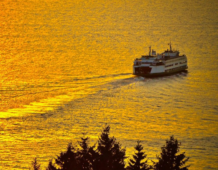 A ferry boat makes its way through the Puget Sound in the golden sunset waters