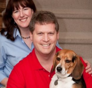 The Innkeeper, her husband, and her dog sitting on the stairs inside the home together