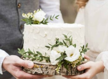 couple holding layer of wedding cake trimmed with white flowers