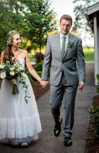 The innkeepers son and daughter in law walk hand in hand together smiling after the wedding