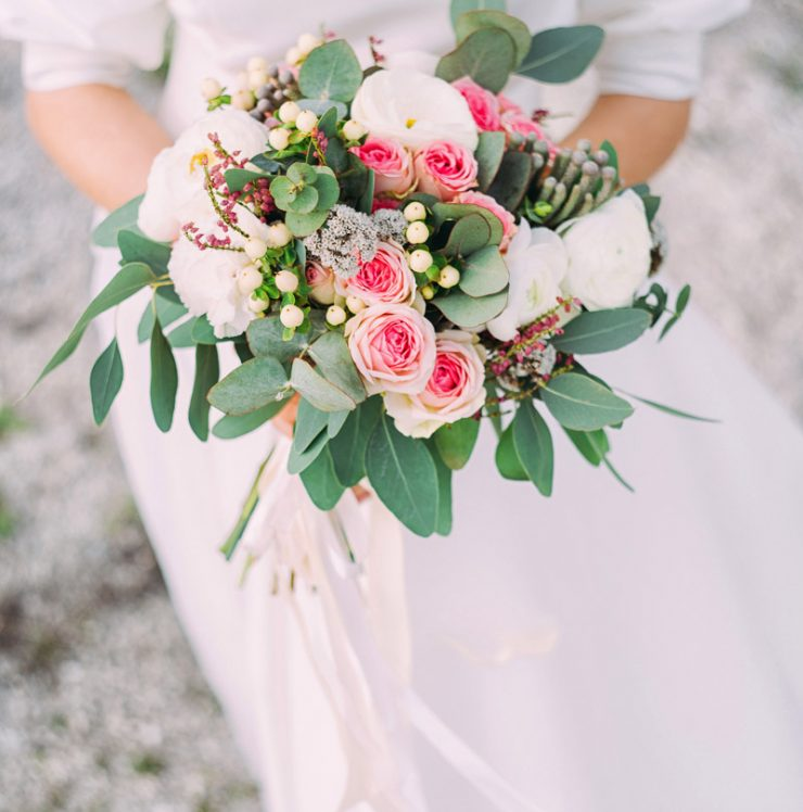A woman in a white wedding dress holds pink flowers up close