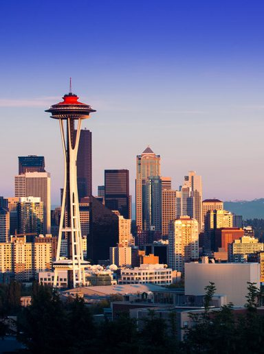 Seattle, Washington with space needle and mountains in background under bright blue sky
