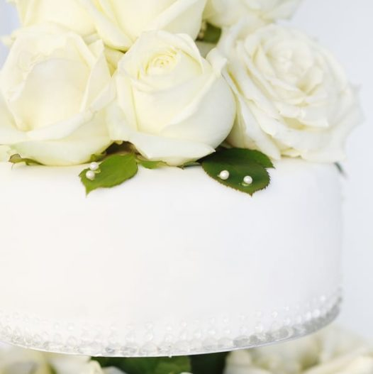 White wedding cake topped with real white roses