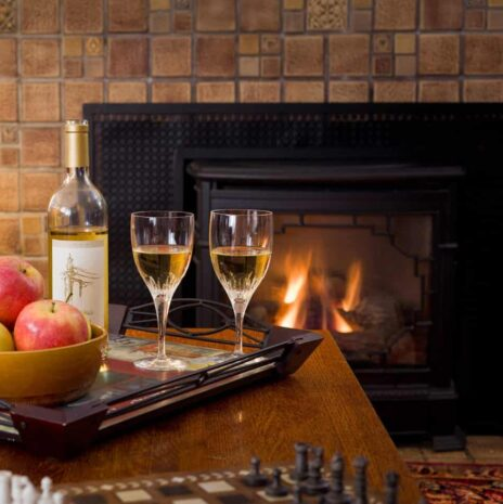 The fireplace is on with two glasses of chardonnay in front and a bowl of apples on the table