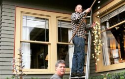 The father and son putting up the Christmas lights