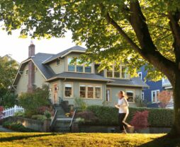 A woman jogs by in the early morning light in front of the Greenlake Guest house