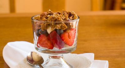 Yogurt parfait with a spoon on the plate looks sweet and delicious