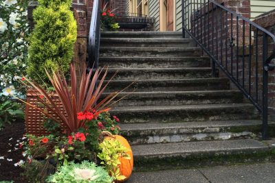 The front entrance around fall is decorated with pumpkins and fall colored floral