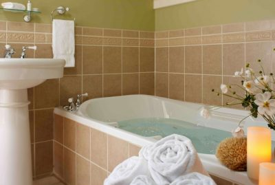 Inside the bathroom with a full tub and candle lit on the side of the tub for a relaxing weekend